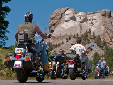 Presidents looking down on cyclists during Sturgis Motorcycle Rally